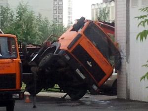 Эвакуатор завалился на здание магазина